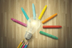 Bright light bulb and crayon. Creative Idea Concept. Closeup of a bright light bulb and multicolor crayon with wooden background Stock Photos