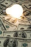 Bright Light Bulb and Dollar Stock Photography