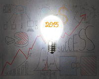Bright 2015 light bulb illuminated dark doodles wall. With business concept graph background Royalty Free Stock Photo