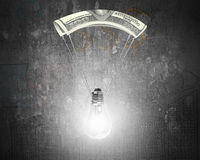 Bright light bulb with money parachute Stock Photo