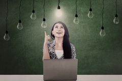 Bright light bulb and woman. Businesswoman looking at lit light bulb in front of laptop Stock Photos