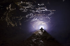 Bright light in a dark cave. Bright light in a dark mysterious cave Royalty Free Stock Photography