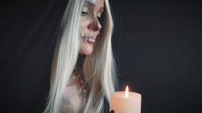 Bright light of fire from burning candle, girl with white hair in dark room. Nun with creaive sweet skull prays for joyful afterlife of dead, lady with dark stock video