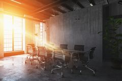 Bright light streaming into industrial office. Bright, warm sunset light streaming through windows into an industrial style office with table and chairs Royalty Free Stock Photo
