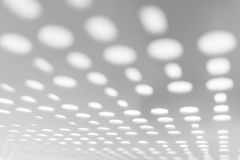 Bright light through white metal panel for blurred abstract pattern and blurred background. Perspective view. Selective focus Stock Photos