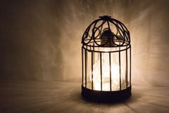 Bright lightbulb in cage. Bright glowing lightbulb inside of metal birdcage Stock Photography