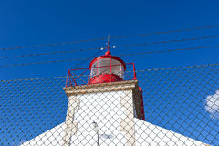 Bright Lighthouse against Blue Sky Background Royalty Free Stock Photo