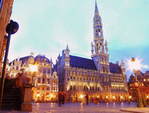 Bright lights in Grand Place, Brussels. The capital of Belgium early evening in a slight time lapse as tourists enjoy the historic sights in the main square in Stock Photos
