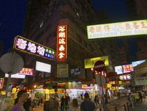 Bright Lights Of Hong Kong -- Crowded City Street. Bright neon lights on signs at a bustling intersection market in Hong Kong with restaurants and shops stock image