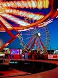 Bright lights on rides at amusement park. Amusement park rides at dusk at a county fair stock images