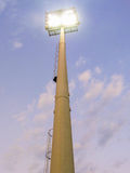 Bright lights in a stadium. Mast with bright white lights in a stadium with sky in background Stock Images