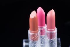 Bright lipsticks on a black background Stock Photos
