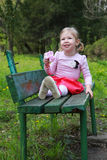 The bright little girl sits on the bank of a park, smiles Royalty Free Stock Images