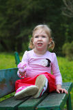The bright little girl sits on the bank of a park Royalty Free Stock Images