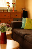 Bright living room. Detail of a living room with couch, cushions table and flowers stock photo