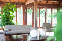 Bright living room with big windows. Bright living room with a beige sofa, coffee table with sphere illuminator, some house plants and big windows Royalty Free Stock Photography