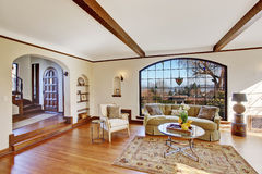 Bright living room in luxury english tutor house. Soft ivory bright living room with arch window, hardwood floor and ceiling beams royalty free stock photos