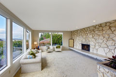 Bright living room with rock wall trim and fireplace Stock Photo