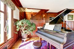 Bright living room with wooden panel trim walls and grand piano Royalty Free Stock Photos