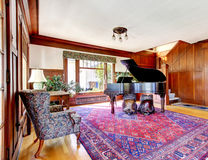 Bright living room with wooden panel trim walls and grand piano Royalty Free Stock Image