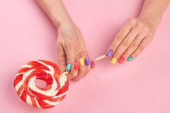 Bright lollipop in female hands. Female hands with multicolor summer nails holding tasty big lollypop on pink background, top view Royalty Free Stock Photography