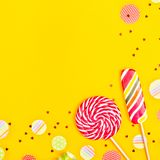 Bright lollipops with multi-colored candy on yellow stock photo