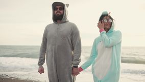 Bright and loving spouses in glasses holding hands in a unicorn and cat costume. Bright and in love with each other, the wife and husband in sunglasses hold stock footage