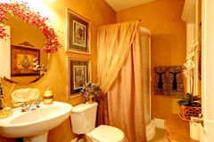 Bright luxury bathroom in gold color. Bright luxury bathroom wiht  vivid golden walls, orange curtains and white washbasin stand with toilet Royalty Free Stock Images