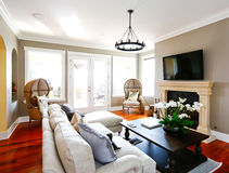 Bright luxury living room with fireplace and tv stock photography