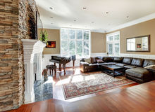 Bright luxury living room with stone fireplace and cherry hardwood. Luxury living room with stobe fireplace and leather sofas, cherry hardwood and nice rug Royalty Free Stock Photography