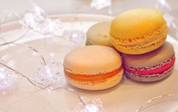 Bright macaroons lie on a plate and a garland with lights stock photos