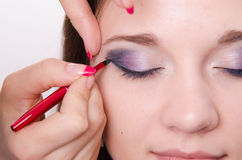 Bright makeup. Makeup artist begins to draw arrows Royalty Free Stock Photography