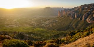 Bright Mallos of Riglos at sunset from top of the mountain. Wide panorama of Mallos of Riglos at sunset from top of viewpoint with bright sun Stock Photography