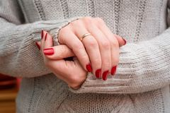 Bright red manicure. Bright manicure on female hands. Woman in a gray knitted sweater shows red manicure closeup Royalty Free Stock Photography
