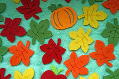 Bright Maple leaves out of felt on a light green fabric as a bac Royalty Free Stock Images