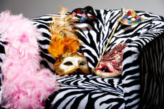 Bright masquerade masks on retro chair Stock Photos
