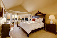 Bright master bedroom with vaulted ceiling and beige carpet floor. Royalty Free Stock Image