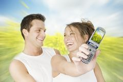Bright memories. Happy young couple holding a cell-phone with a bright flower screen-saver over a colorful dynamic background stock images