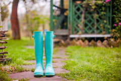 Bright mint rubber boots in the garden summer stock image