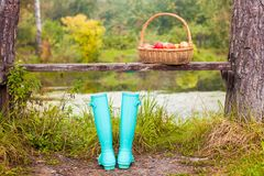 Bright mint rubber boots and straw basket on a Royalty Free Stock Image