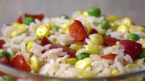 Bright mix of rice, corn, peas and red sweet pepper in glass bowl, 4K dolly shot stock video