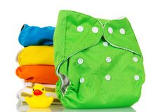 Bright modern environmentally friendly diapers and rubber duckli. Bright modern environmentally friendly diapers and a rubber duckling isolated on white Stock Photography
