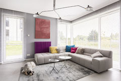 Window blinds, couch and artwork. Bright modern living room with comfortable corner couch, artwork, coffee table, window blinds and rug stock photo