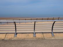 Bright modern metal railings along the seaside promenade in blackpool lancashire with concrete sea wall with ocean and blue sky. Bright modern metal railings royalty free stock photo