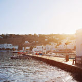 Bright Morning Sun on the Dock of Mykonos Town. Morning sunlight bathing the dock lined with cute boats. Shoreline pictured is the shore of Mykonos town on Stock Photos