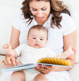 Bright mother showing images in a book to her son Stock Image