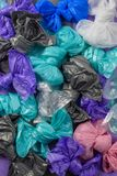 Bright multi-colored plastic garbage bags rolled into bows stock image