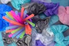 Bright multi-colored plastic tubules in a purple glass on the background of garbage bags royalty free stock photography