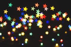 Bright multi-colored stars on a black background. Bokeh, soft focus royalty free stock photo