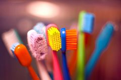 Bright multi-colored toothbrushes standing in a glass with a blurred background stock image
